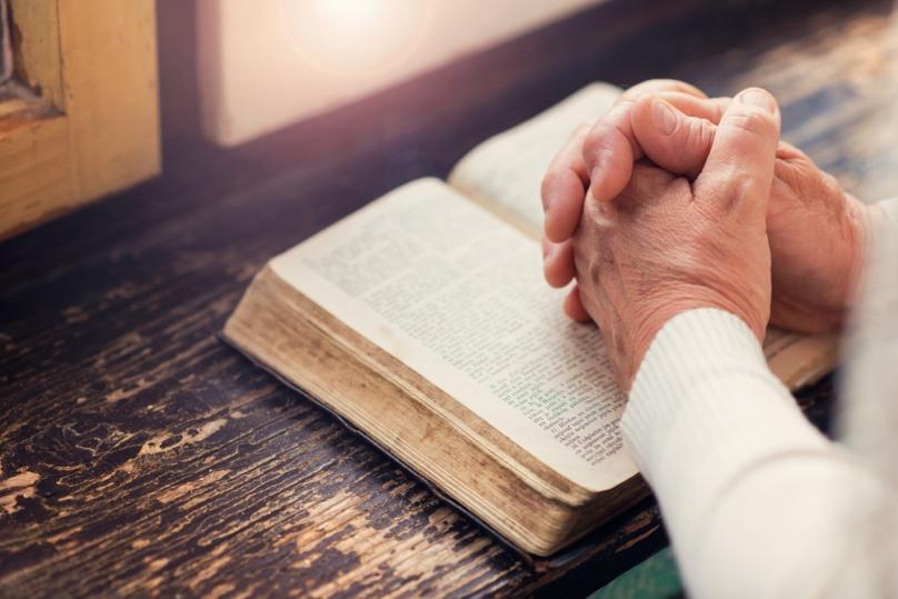 shutterstock_334942148-older-woman-praying-hands-bible.jpg
